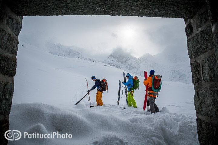Skiers putting on skins outside hut