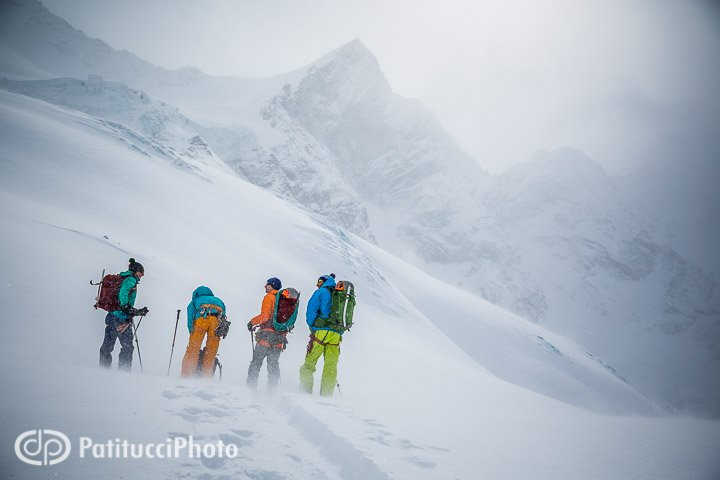 Backcountry skiers stopped on a cold, cloudy day