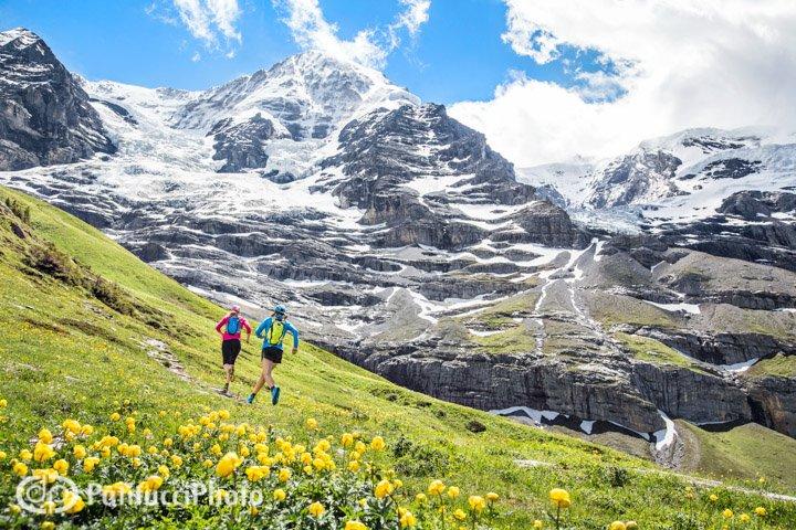 Two women running mountain trails from Lauterbrunnen to Kleine Scheidegg, in the Berner Oberland region of Switzerland