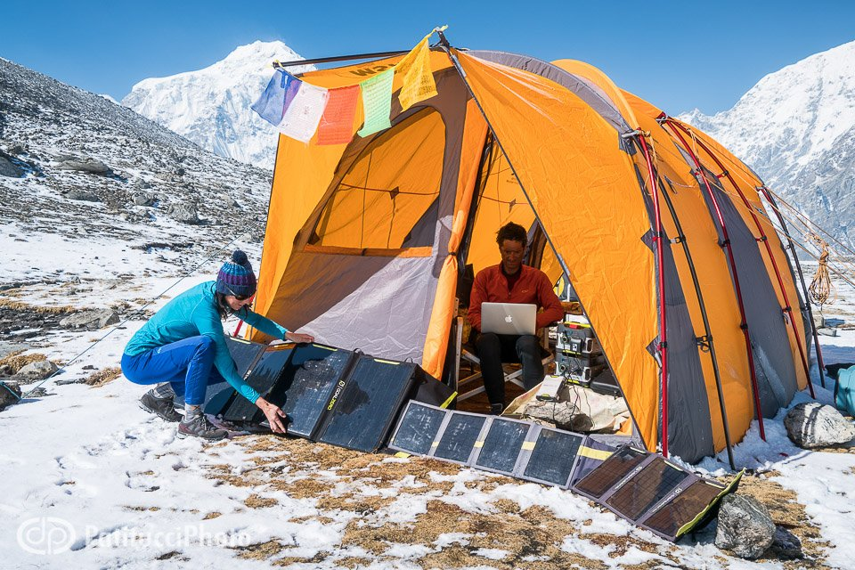 Two people at a basecamp during a Himalayan trek using solar panels to power their technology, including a laptop computer. Tibet.