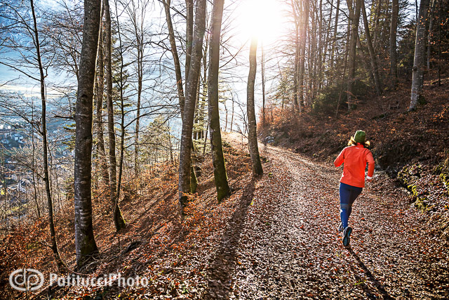 Woman winter running on forest road