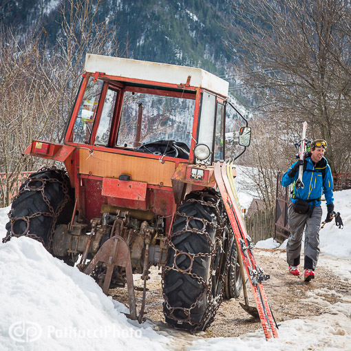 Skier walking past tractor