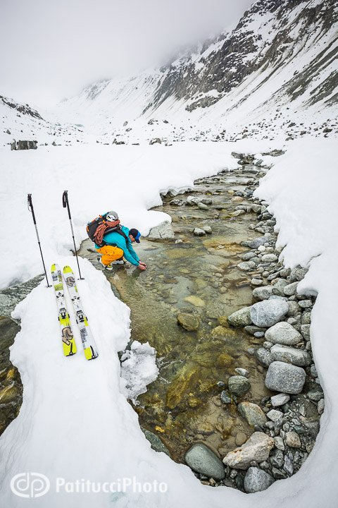 Skier drinking water from creek