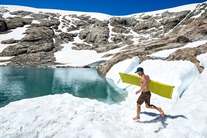 A hiker plays in the snow with a sleeping pad along the shores of a high alpine lake, Switzerland