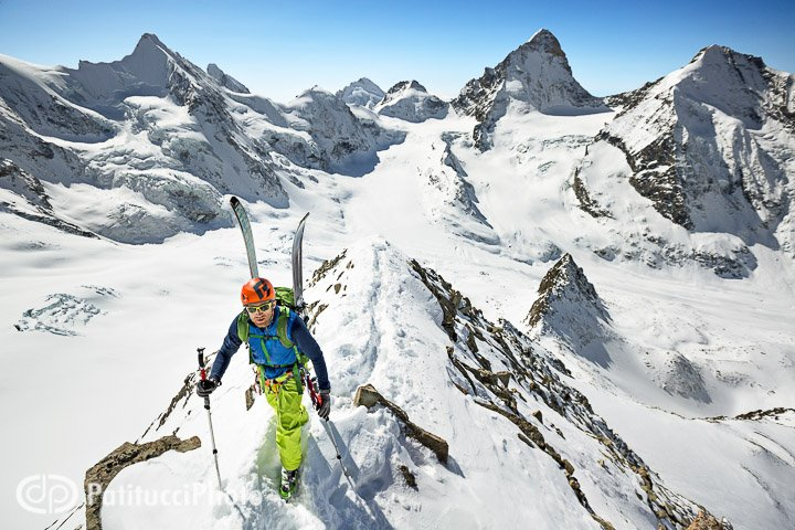 A backcountry skier carrying his skis while climbing the Blanc de Moming, a classic ski peak in the Swiss Alps Wallis Region. Skiers are rewarded with a 2000 meter descent to Zinal.