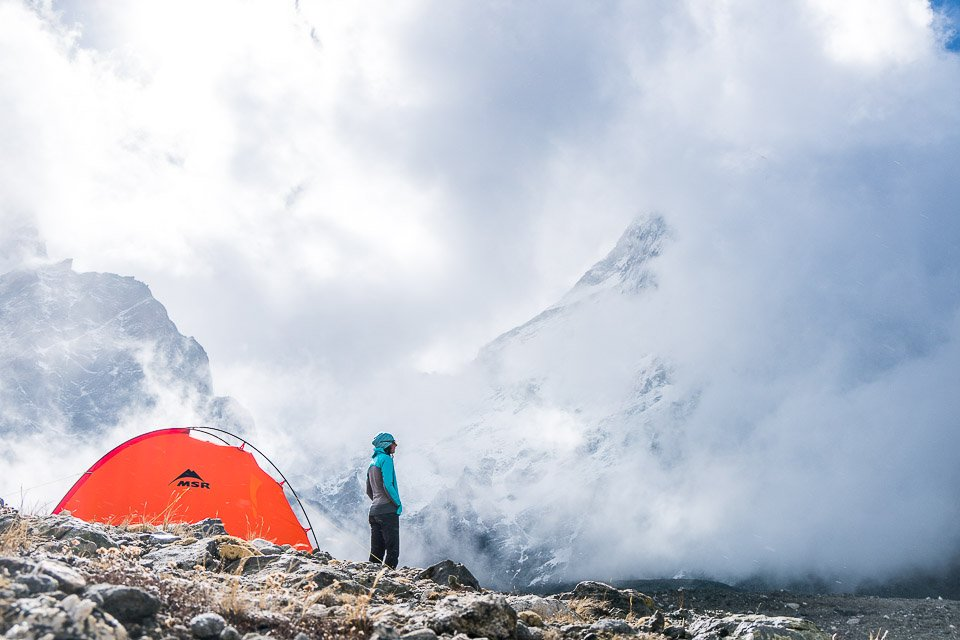 A woman stands next to her tent watching as the clouds begin to open and a peak above becomes visible, Tibet
