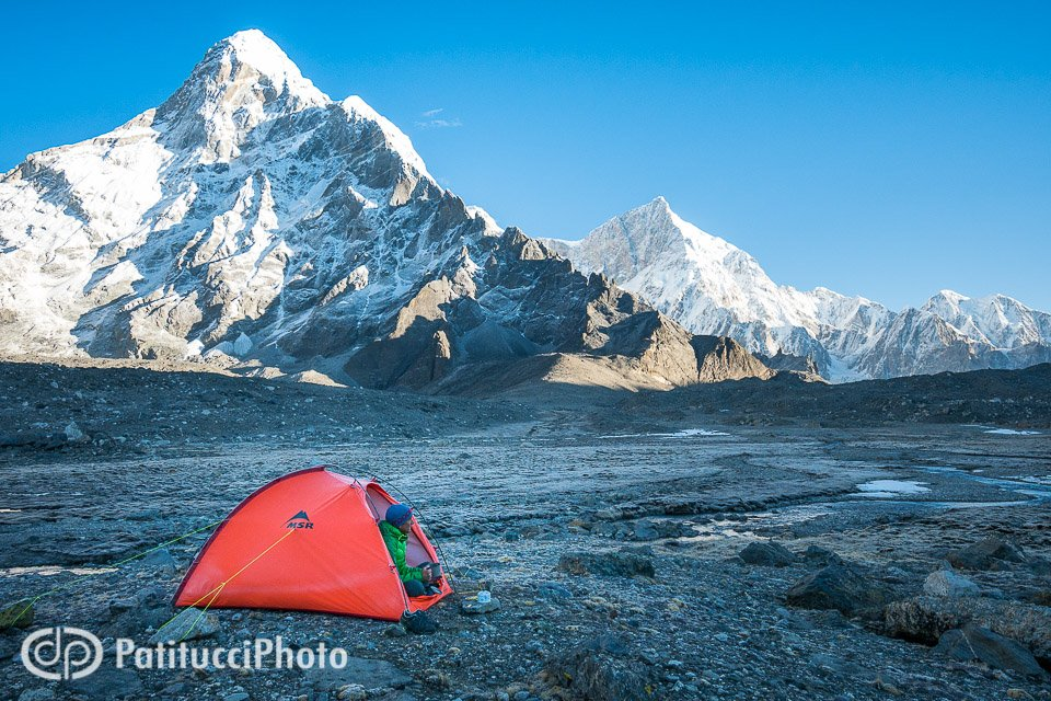 A man sits at his tent using a camp stove as the first light of sunrise begins to hit the massive mountain, Nyanang Ri, above camp, Tibet