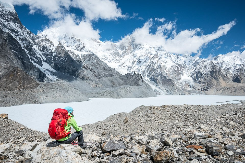 A woman sits looking out on a frozen Himalayan lake high in the Tibet Himalaya