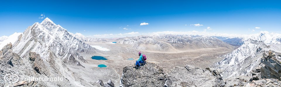 A lone hiker sits on top of a small rock summit in the Tibet Himalaya with distant views to the Tibetan Plateau