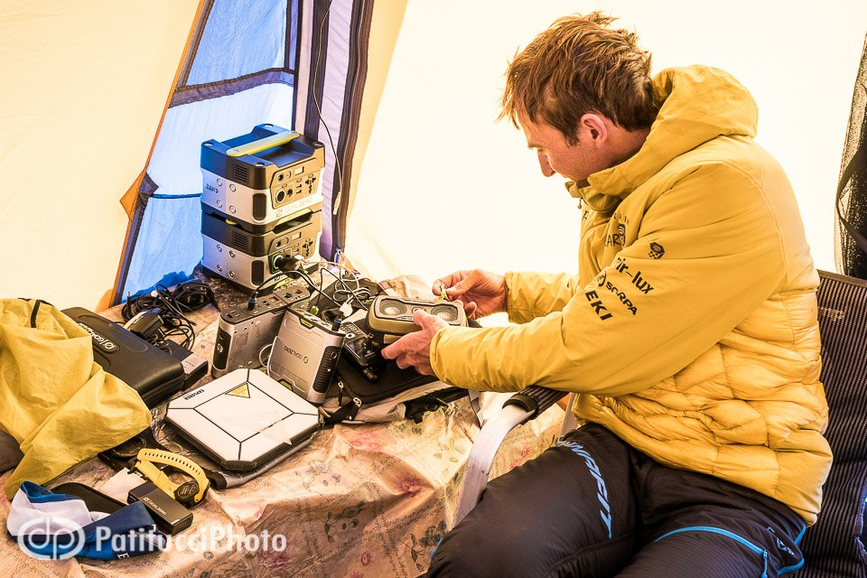 Ueli Steck inside a basecamp tent checking battery power levels from the solar system, during a climbing expedition to the 8000 meter peak Shishapangma, Tibet